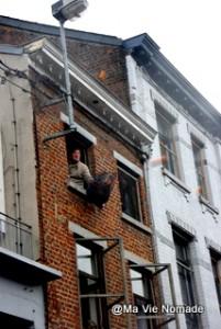 Un homme à sa fenêtre s'amuse à attraper des oranges